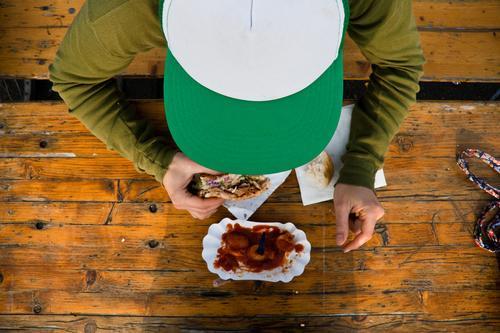 Zum Frühstück Currywurst Mensch Mann Jugendliche grün Ernährung Erwachsene Essen maskulin Lebensmittel Bank Vogelperspektive Gemüse Appetit & Hunger Mütze Brot