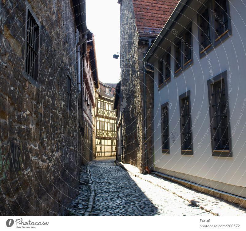 Durch diese enge Gasse wird er kommen... Haus Sonnenlicht Stadtzentrum Altstadt Menschenleer Gebäude Mauer Wand Fenster Straße Kopfsteinpflaster alt historisch