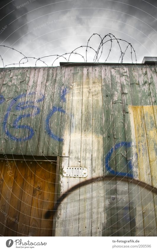 Das Geheimnis Stadt Wolken dunkel Wand Holz grau Mauer Graffiti Tür hoch trist kaputt bedrohlich Zeichen Verfall trashig
