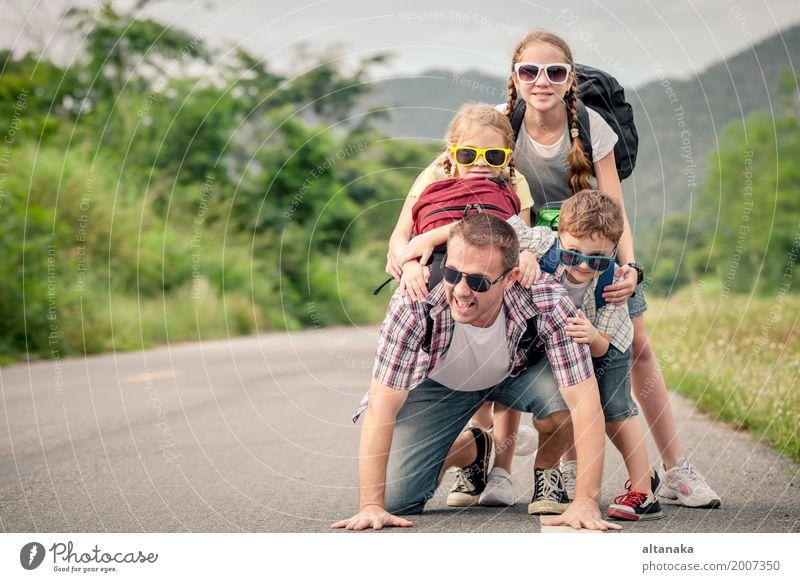 Vater und Kinder, die zur Tageszeit auf die Straße gehen. Lifestyle Freude Glück Freizeit & Hobby Ferien & Urlaub & Reisen Ausflug Abenteuer Freiheit Sommer
