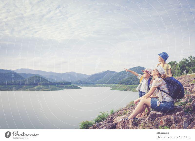 Glückliche Familie, die nahe dem See zur Tageszeit steht. Mensch Kind Frau Natur Ferien & Urlaub & Reisen Mann Sommer Freude Berge u. Gebirge Erwachsene