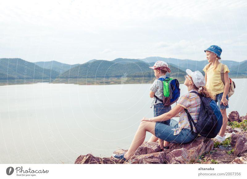 Glückliche Familie, die nahe dem See zur Tageszeit steht. Ferien & Urlaub & Reisen Sommer Berge u. Gebirge Lifestyle Gesundheit Freiheit Tourismus Ausflug