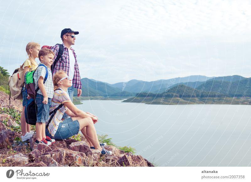 Glückliche Familie, die nahe dem See zur Tageszeit steht. Gesundheit wandern Mensch Kind Frau Erwachsene Mann Eltern Mutter Vater Bruder Schwester Freundschaft