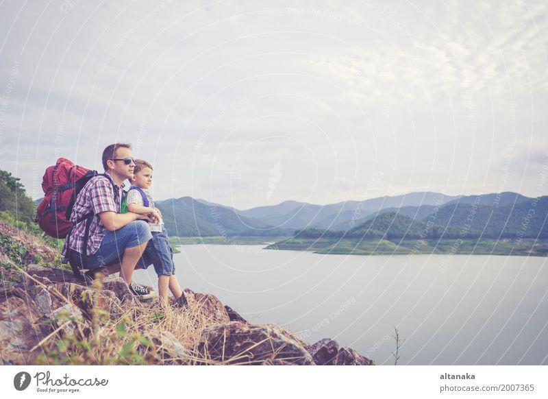 Vater und Sohn, die nahe dem See zur Tageszeit stehen. Mensch Kind Natur Ferien & Urlaub & Reisen Mann Sommer Freude Berge u. Gebirge Erwachsene Lifestyle Liebe