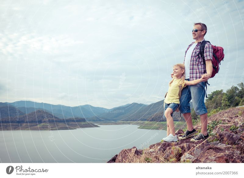 Vater und Tochter, die nahe dem See zur Tageszeit stehen. Mensch Kind Natur Ferien & Urlaub & Reisen Mann Sommer Freude Mädchen Berge u. Gebirge Erwachsene