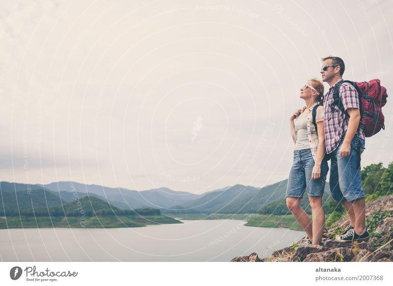 Glückliche Familie, die nahe dem See zur Tageszeit steht. Mensch Natur Ferien & Urlaub & Reisen Mann Sommer Erholung Freude Strand Berge u. Gebirge Erwachsene