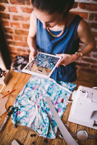 Junger weiblicher Blogger, der Foto des Kleides mit Tablette macht Design Arbeit & Erwerbstätigkeit Beruf Büro Handwerk Business Bildschirm Fotokamera