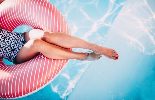 Frau, die auf aufblasbarem Ring im Swimmingpool sich entspannt Lifestyle Spa Schwimmbad Ferien & Urlaub & Reisen Sommer feminin Junge Frau Jugendliche