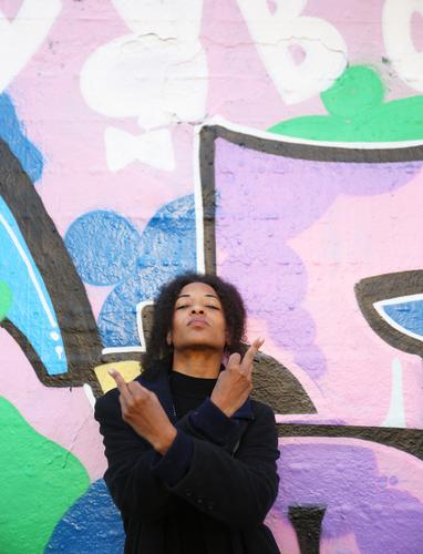 . feminin Frau Erwachsene 1 Mensch Pullover Haare & Frisuren brünett Locken Afro-Look Zeichen Graffiti beobachten Blick rebellisch Wachsamkeit Leben Ausdauer