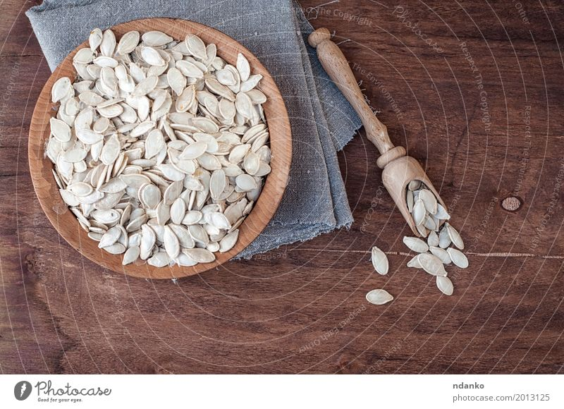 Ungeschälte Kürbiskerne in einer hölzernen Schüssel Gemüse Schalen & Schüsseln Löffel Tisch Küche Holz frisch oben braun grau weiß Samen Snack Feinschmecker Top