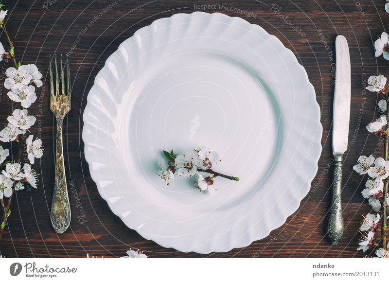 Weiße Platte mit einer Gabel und Messer auf einer braunen Holzoberfläche alt weiß Blume Speise Essen oben Metall retro Aussicht Tisch Platz Küche Restaurant