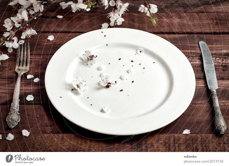 Porzellanplatte mit einem wilkyo und einem Messer auf einer braunen Tabelle Mittagessen Abendessen Teller Besteck Gabel Tisch Küche Restaurant Pflanze Blume