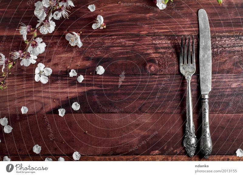 Tischbesteck Messer und Gabel auf einem braunen Tisch Besteck Küche Restaurant Werkzeug Blume Holz Metall alt oben weiß Kulisse Silberwaren speisend