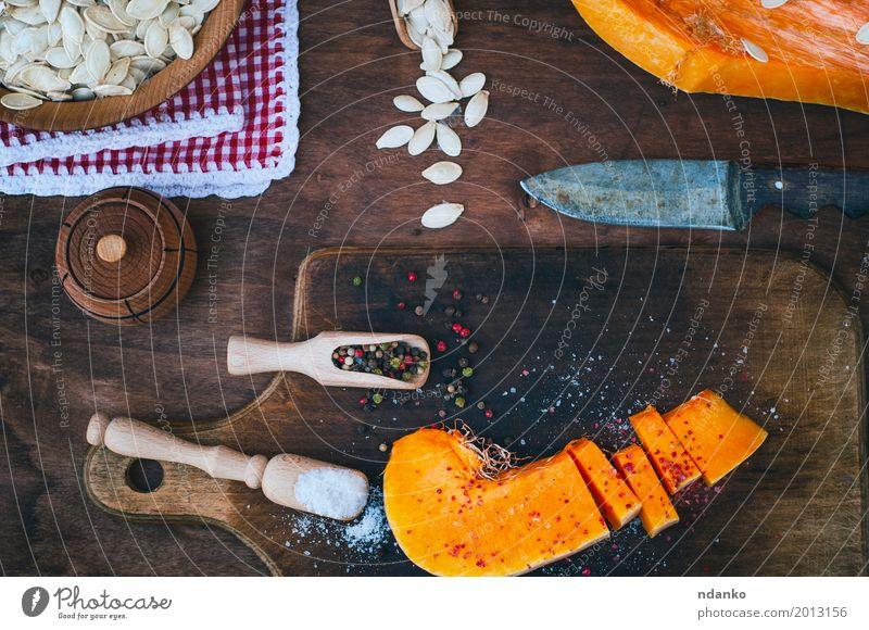 Stück frischer Kürbis mit Salz und Pfeffer Lebensmittel Gemüse Kräuter & Gewürze Ernährung Messer Löffel Holz Essen oben braun orange weiß Paprika Koch Zutaten