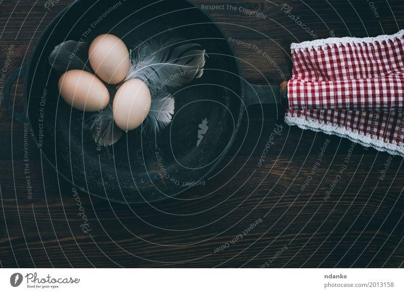 Hühnereier in einer schwarzen Gusseisenpfanne Essen gelb natürlich Holz braun Ernährung frisch Feder Tisch Küche Frühstück Tradition Mahlzeit ländlich rustikal