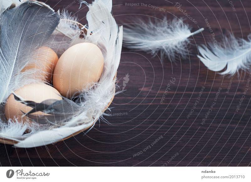 Drei Hühnereier in einem Korb mit Federn Farbe weiß Essen gelb Holz Lebensmittel braun frisch Tisch Küche Frühstück Tradition Mahlzeit ländlich Konsistenz