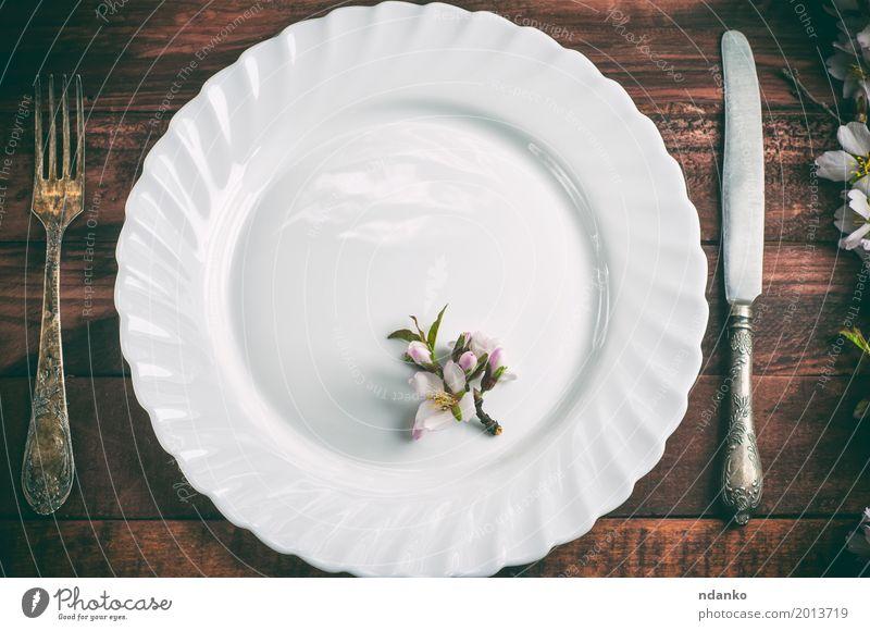 Platte mit einer Gabel und Messer auf einer braunen Holzoberfläche Mittagessen Abendessen Teller Besteck Tisch Küche Restaurant Blume Metall alt oben retro weiß
