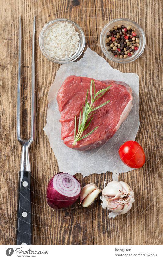 rohes Steak auf Holz Fleisch Kräuter & Gewürze Gabel Papier frisch rot weiß Ausfischt Rindersteak Rindsfleisch Knoblauch Tomate Zwiebel Salz Fleischgabel