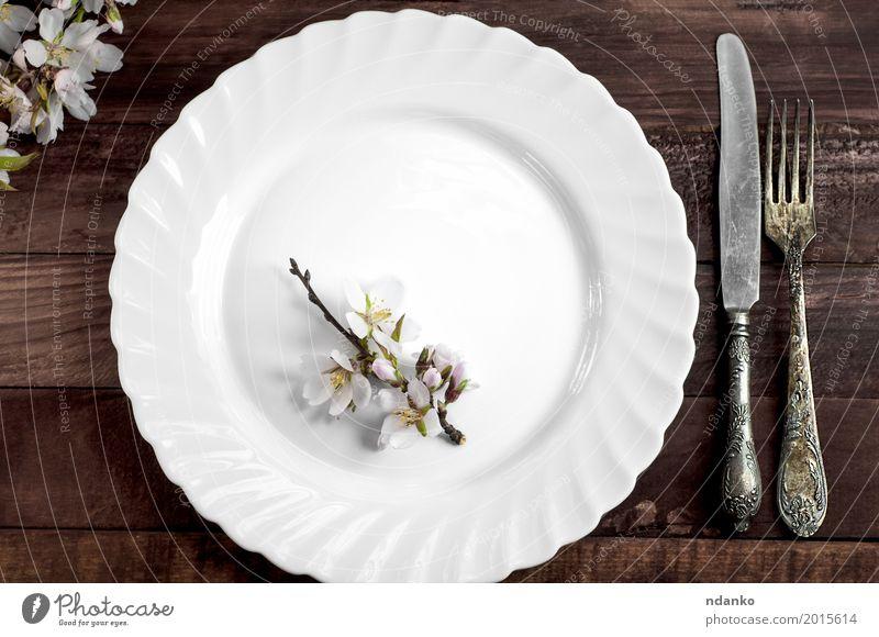 Weißer Teller mit Eisenbesteck Mittagessen Abendessen Besteck Messer Gabel Tisch Küche Restaurant Blume Platz Holz Metall Stahl alt oben retro braun weiß Speise