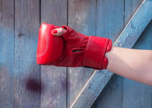 Rechte Handfrau in einem roten Boxhandschuh Mensch Frau alt blau Erwachsene Sport feminin Holz Mode retro Kraft Erfolg Finger Macht