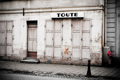 TOUTE Dorf Stadtrand Altstadt Haus Ruine Bauwerk Gebäude Architektur Mauer Wand Fassade Fenster Tür Schriftzeichen alt Armut authentisch kaputt grau