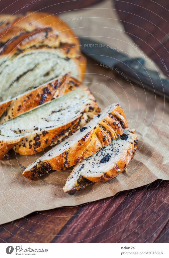 Geschnittene Rolle mit Mohn und Rosinen schwarz Essen Holz braun oben frisch Tisch Papier Frühstück Dessert Brot Backwaren Messer Mahlzeit Scheibe