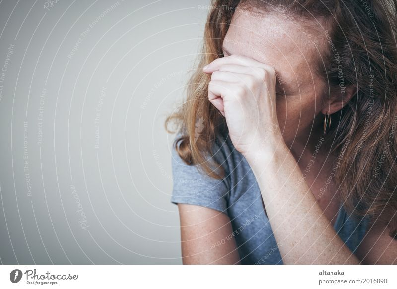 eine traurige Frau, die an einer Wand sitzt und ihren Kopf in den Händen hält Lifestyle Gesicht Mensch Mädchen Erwachsene Familie & Verwandtschaft Traurigkeit