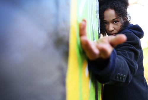 . feminin Frau Erwachsene 1 Mensch Kunst Künstler Kunstwerk Mauer Wand Mantel Haare & Frisuren brünett langhaarig Locken Afro-Look Graffiti beobachten Blick