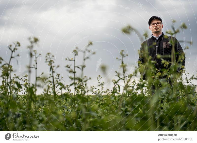 Bewölkt und Mann im Unkraut 1 Pflanze grün Junger Mann Wolken grau Feld stehen warten Landwirtschaft verloren schlechtes Wetter verirrt irre