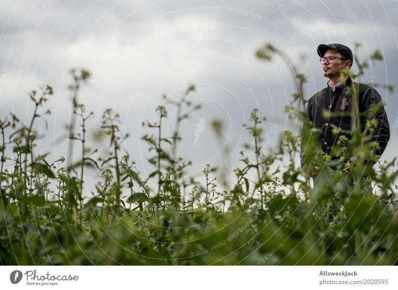 Bewölkt und Mann im Unkraut 2 Wolken graue Wolken schlechtes Wetter Feld grün Pflanze Junger Mann verloren stehen warten Waldmensch verirrt irre Landwirt