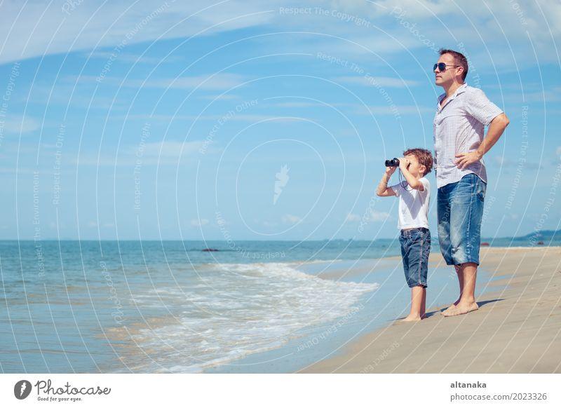 Vater und Sohn mit Fernglas stehen am Strand zur Tageszeit. Konzept der freundlichen Familie. Lifestyle Freude Leben Erholung Freizeit & Hobby Spielen