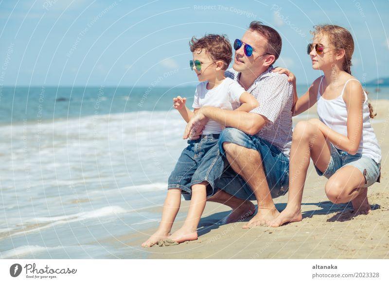 Vater und Kinder, die am Strand zur Tageszeit sitzen. Natur Ferien & Urlaub & Reisen Sommer Sonne Meer Erholung Freude Erwachsene Leben Lifestyle Liebe Junge