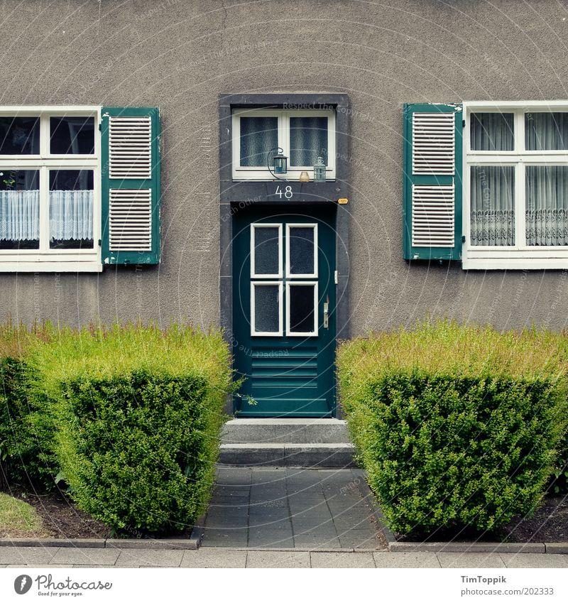 Im Wunderland #5 grün Haus Fenster grau Architektur Tür Fassade Treppe Ordnung trist Häusliches Leben Laterne Eingang Gardine Hecke Pflastersteine