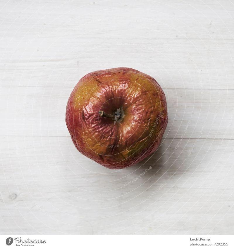 Früher war alles besser. Apfel Vogelperspektive alt Falte Frucht Stengel weich rot gelb rotgelb Holztisch weiß Maserung Apfelschale Ernährung süß verschrumpelt