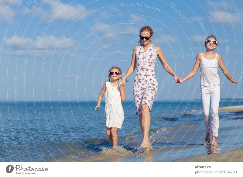 Mutter und Kinder, die am Strand zur Tageszeit spielen. Lifestyle Freude Leben Erholung Freizeit & Hobby Spielen Ferien & Urlaub & Reisen Ausflug Abenteuer