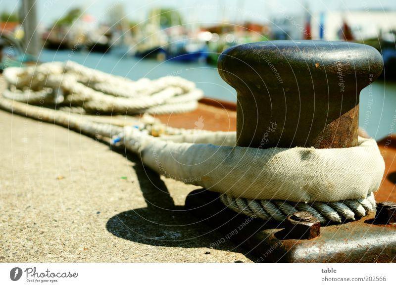 ganz doll festhalten . . . Ferien & Urlaub & Reisen Verkehr Schifffahrt Hafen Seil Beton Metall Knoten liegen braun grau schwarz Sicherheit Poller Farbfoto