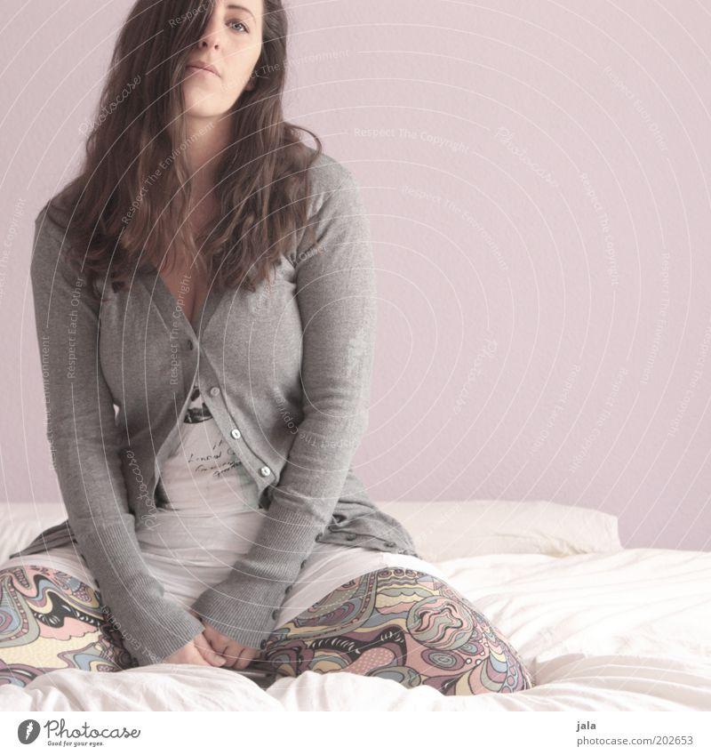 und nu? Frau Mensch feminin grau Erwachsene rosa Bekleidung sitzen Bett Langeweile brünett Gesichtsausdruck langhaarig Junge Frau Möbel Strickjacke