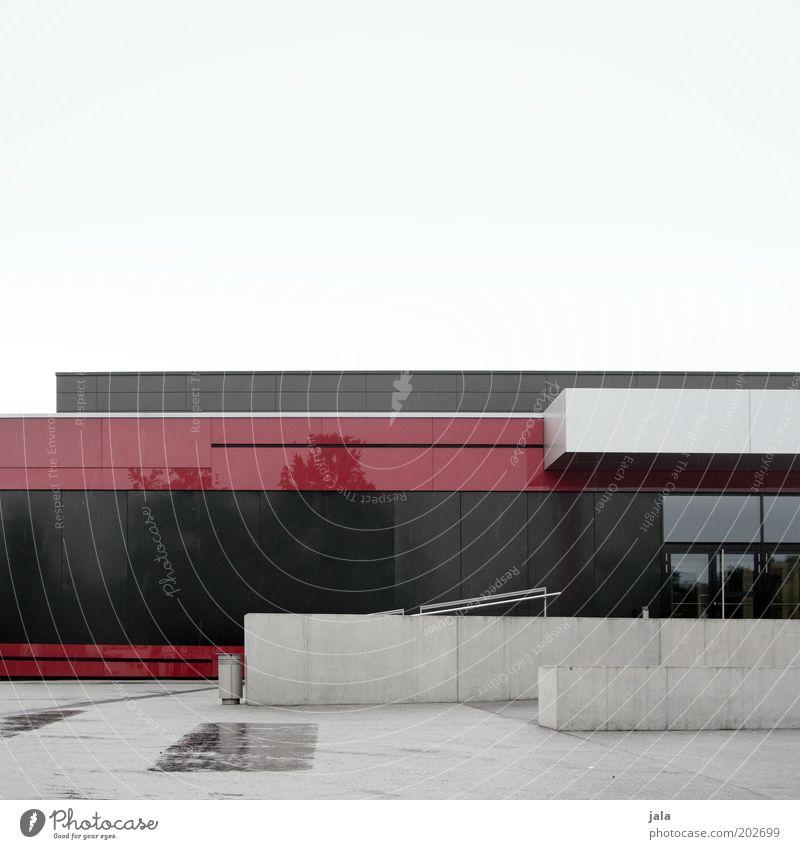 mehrzweckhalle Menschenleer Haus Platz Bauwerk Gebäude Architektur Halle Mauer Wand Treppe Fassade Tür groß trist grau rot schwarz Farbfoto Außenaufnahme