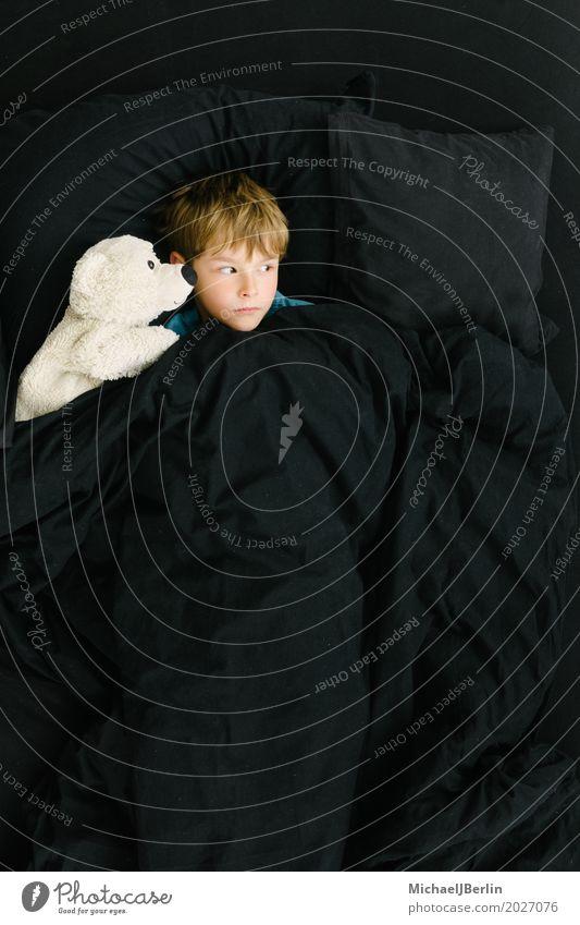 Schulkind im Bett mit Plüschtier schauen ängstlich zur Seite Mensch maskulin Kind Junge Kindheit 1 3-8 Jahre Teddybär Stofftiere liegen Blick schlafen schwarz