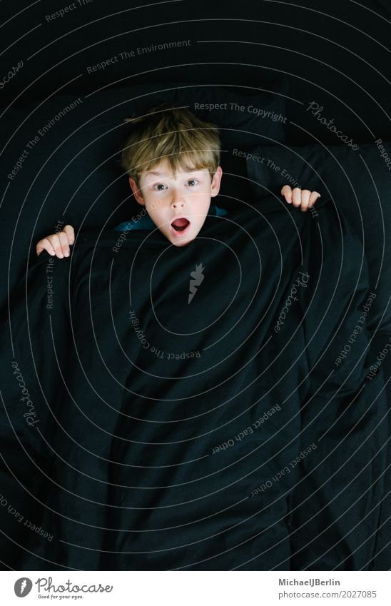 Junge schaut überrascht unter schwarzer Bettdecke Schlafzimmer Mensch maskulin Kind 1 3-8 Jahre Kindheit blond Gefühle Überraschung Angst Entsetzen Farbfoto