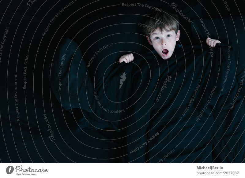 Junge mit schockiertem Blick unter schwarzer Bettdecke Kind Mensch Gefühle Kopf Angst maskulin Kindheit Sorge Decke Entsetzen erschrecken 3-8 Jahre Unglaube