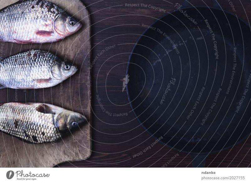Drei lebende Karpfenfische in einer Skala auf einem Küchenbrett schwarz Essen natürlich Holz braun oben frisch Tisch Fisch Kräuter & Gewürze Fleisch Top