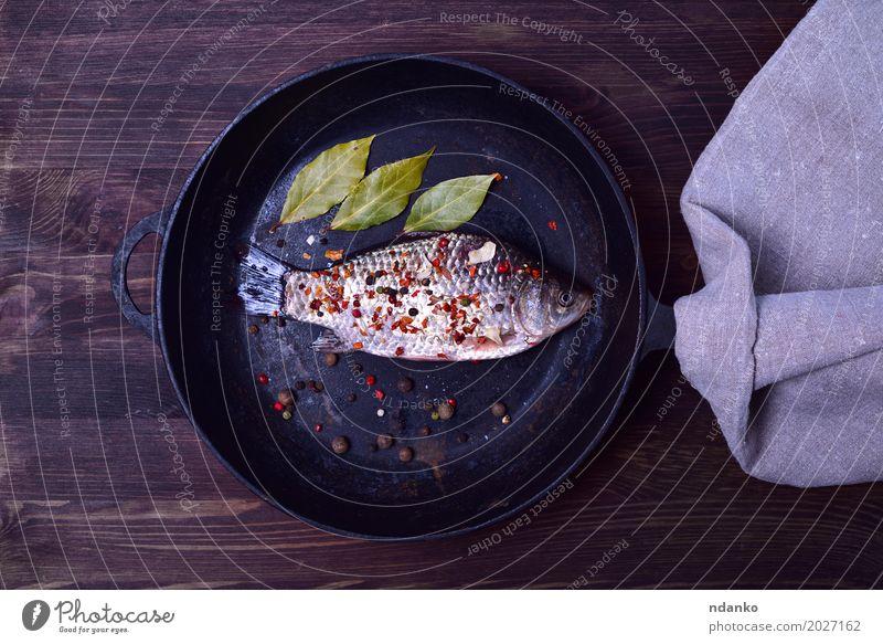 Crucian Karpfen in Gewürzen auf einer schwarzen Gusseisen Bratpfanne Natur grün Blatt Essen natürlich Holz Lebensmittel braun oben Ernährung frisch Tisch Fisch