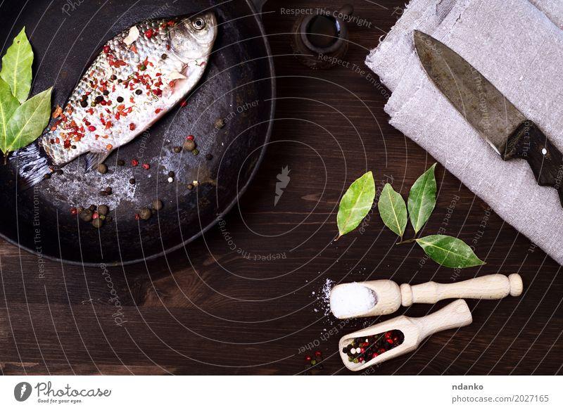 Fisch crucian in einer Gusseisenbratpfanne mit Gewürzen Kräuter & Gewürze Ernährung Pfanne Löffel Tisch Küche Essen frisch lecker retro braun schwarz Kruzianer