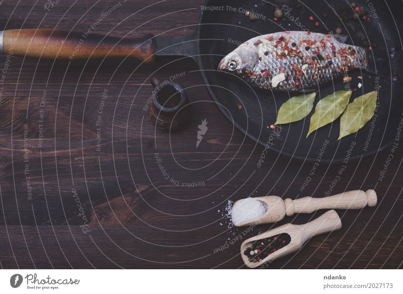 Frisches crucian in einer Bratpfanne Lebensmittel Fisch Kräuter & Gewürze Pfanne Löffel Tisch Küche Fluss frisch retro braun schwarz Kruzianer Salz Paprika Koch
