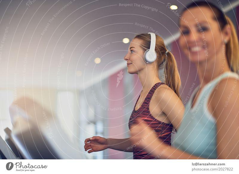 Attraktive Frau mit Kopfhörern auf Tretmühle in der Turnhalle Mensch Jugendliche schön 18-30 Jahre Gesicht Erwachsene Lifestyle Sport Glück Textfreiraum