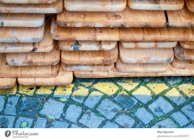 Depot braun gelb grau Pflastersteine Linie Bierbank Biertische Stapel Holz Farbfoto Gedeckte Farben Außenaufnahme Nahaufnahme Detailaufnahme Textfreiraum unten