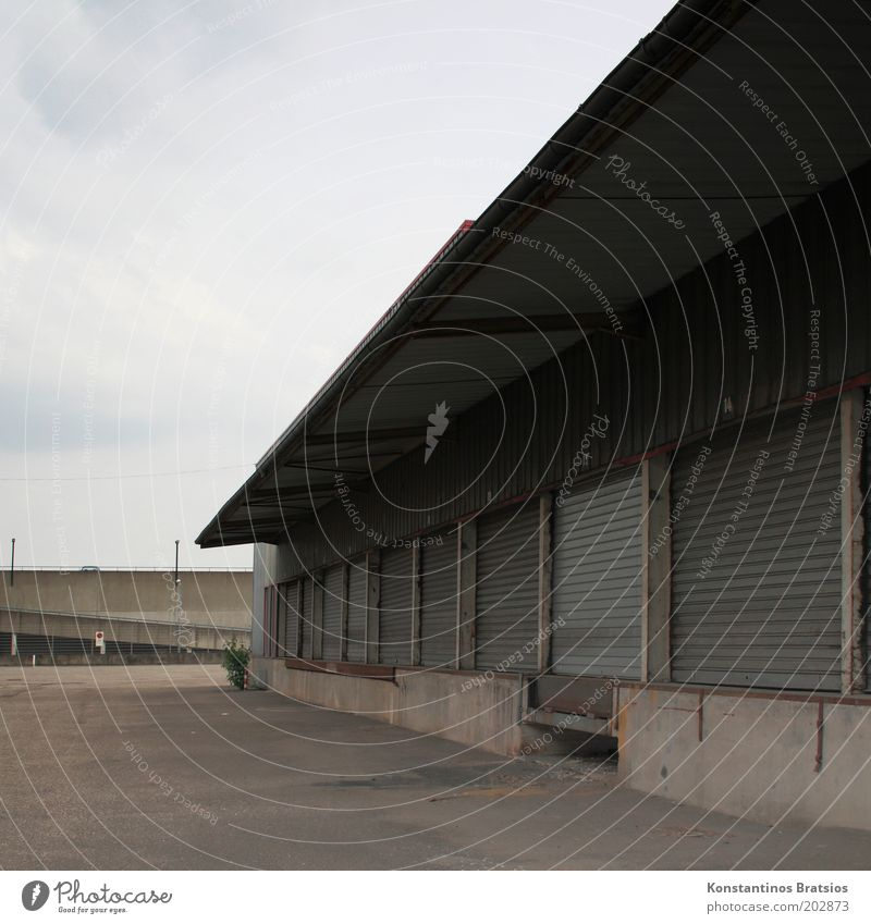 Warenannahme Himmel Wolken Gebäude geschlossen trist Güterverkehr & Logistik Dach einfach Tor Dienstleistungsgewerbe Gewerbe Lagerhalle Versand Rampe
