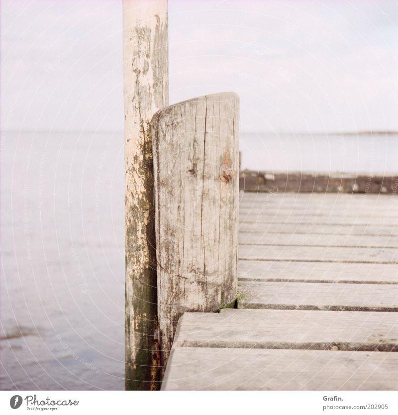 Ruhige See Wasser alt Himmel Winter Strand ruhig Einsamkeit Ferne Holz grau Wege & Pfade Küste dreckig Horizont Steg Holzbrett