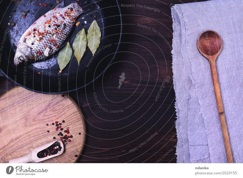 Frischer Karpfen mit Gewürzen in einer schwarzen Gusseisenbratpfanne Essen Lebensmittel braun frisch retro Tisch Fisch Fluss Kräuter & Gewürze Küche Top Löffel